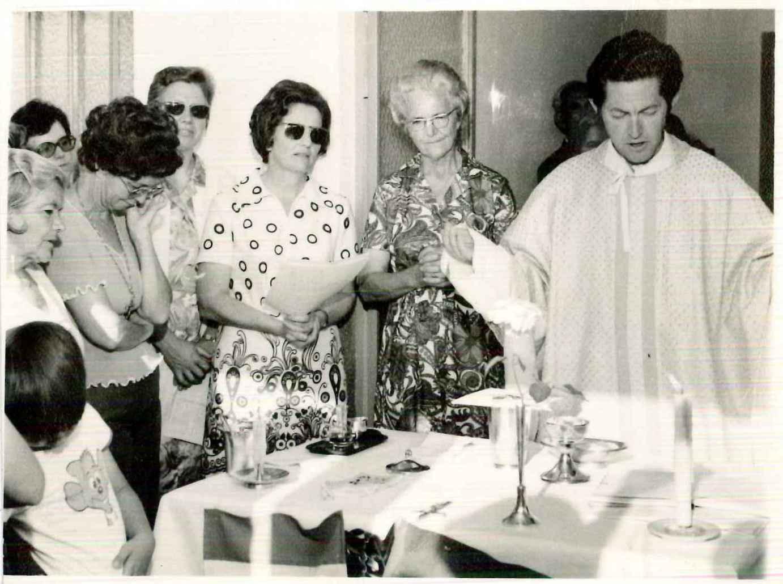 Maria Teresa Winters (ao lado do pároco) participa da celebração ministrada pelo então pároco Waldemar